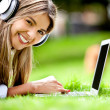 Happy woman downloading music - Stock Photo