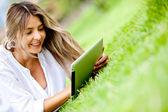 Vrouw met behulp van een tablet buitenshuis — Stockfoto