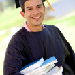 Gradution student carrying books — Stock Photo