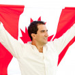 Patriotic man holding Canada flag - Stock Photo