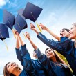 Students throwing graduation hats — Stockfoto