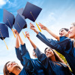 Students throwing graduation hats — Stok fotoğraf