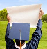 Graduation man holding paper — Stock Photo