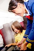 Flight attendant helping a kid — Photo