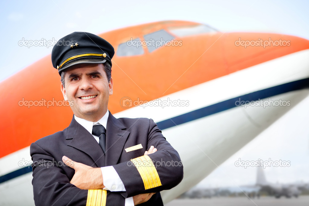 Handsome airplane pilot smiling at the airport — Stock Photo #9297821