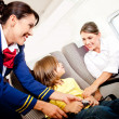 Air hostess helping a kid - Stock Photo