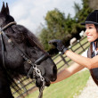 Female jockey stroking horse — Stockfoto #9356251