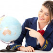 Air hostess pointing at the globe - Stock Photo