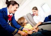Hôtesse de l'air aidant un gamin — Photo