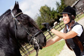 Female jockey stroking a horse — Stock Photo
