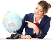 Air hostess pointing at the globe — Stock Photo