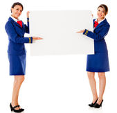 Air hostesses with a banner — Stock Photo
