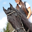 Female jockey riding a horse - Stock Photo
