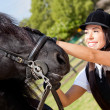 Female jockey stroking horse — Stockfoto #9377452