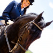 Woman horseback riding - Stock Photo