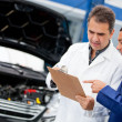 Mechanics fixing a car - Stock Photo