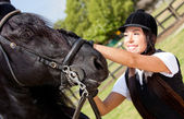 Female jockey stroking a horse — Stockfoto