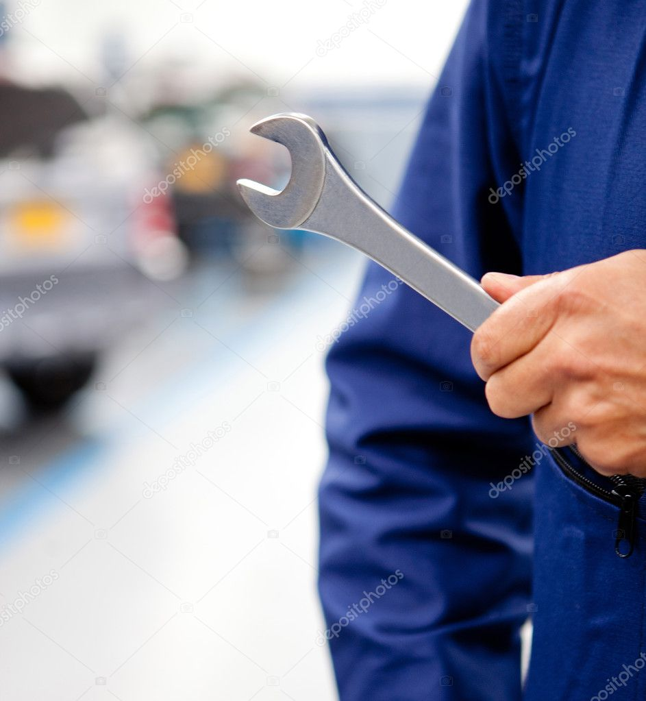 Mechanic with his tool holding a wrench at a garage  Stock Photo #9377522