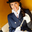 Elegant female jockey smiling - Stock Photo