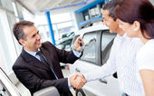 Couple buying a car — Stockfoto