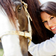 Woman stroking a horse — Stock Photo #9402060