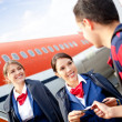 Stock Photo: Flight attendants welcoming passenger