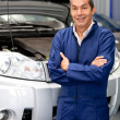 Man working at a car garage - Stock Photo