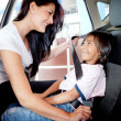 Mother helping to fasten seat belt - 图库照片
