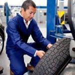 Mechanic fixing car wheel — Stock Photo
