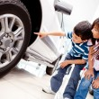 Stock Photo: Kids looking at car wheels