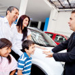 Family with a car salesman — Stock Photo
