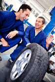 Mechanics working on car puncture — Stock Photo
