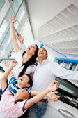 Family celebrating buying a car — Stock Photo