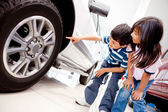 Kids looking at car wheels — Stock Photo