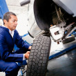 Mechanic placing a wheel — Stock Photo #9557651