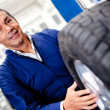 Mechanic changing car wheel - Stock Photo