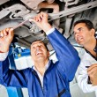 Mechanics working under a car — Stock Photo #9557679