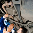 Stock Photo: Mechanics working under car