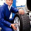 Mechanic fixing a car puncture - Stock Photo