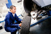 Mechanic placing a wheel — Stock Photo