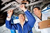 Mechanics working under a car — Stock Photo