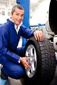 Mechanic fixing a car puncture — Stockfoto