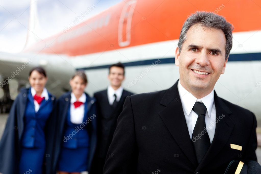 Captain pilot with cabin crew and an airplane at the background — Stock Photo #9557635