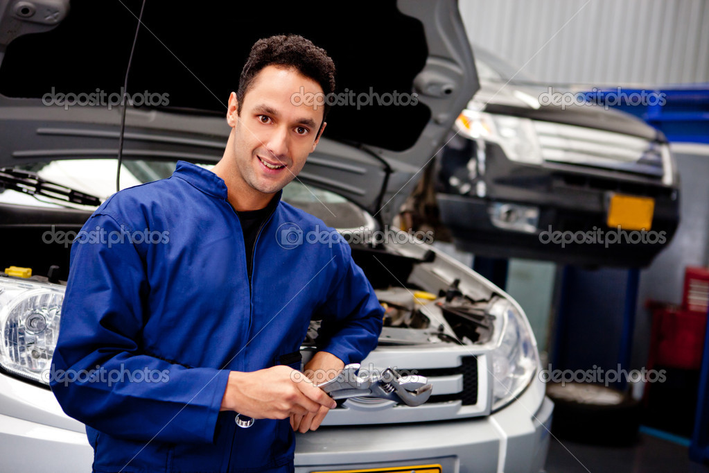 Male mechanic at a car garage holding tools and smiling — Stock Photo #9557658