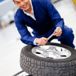 Mechanic fixing car tire — Stockfoto #9632757