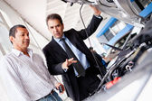 Car salesman with client — Stock Photo
