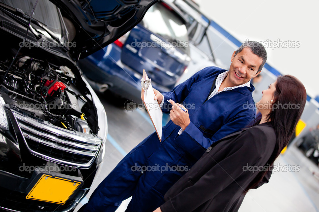 Woman talking with her car mechanic at the repair shop — Stock Photo #9632764