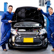 Foto Stock: Mechanics at car repair shop