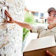 Delivery man ringing doorbell - Stock Photo