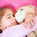 Girl sleeping with teddy bear — Stock Photo